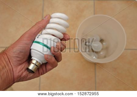 Holding a low energy CFL light bulb with discarded tungsten bulbs in background poster