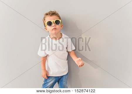 Trendy kid. Cropped photo of little boy in white t-shirt and jeans wearing sunglasses, standing against gray background in studio
