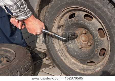 Man is changing winter tire with wheel wrench. Preparing the car for the winter. Repairing punctured tires.