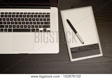 Laptop keyboard and graphics tablet on black table top view