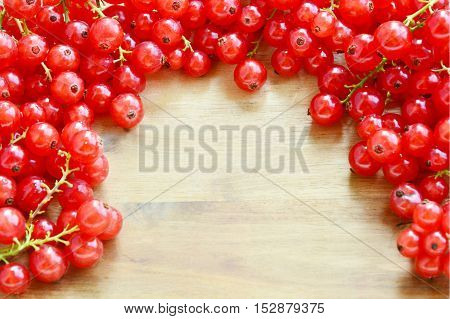 Redcurrant on wooden background with Space for write a message.