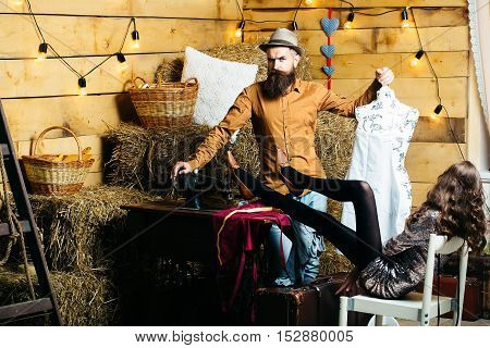 Bearded man tailor or dressmaker in hat and pretty girl sexy fashion model with slim legs at vintage sewing machine in rustic workshop