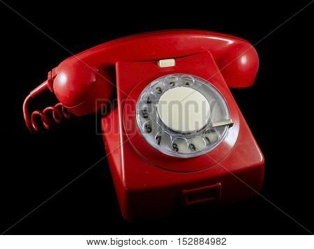 Very old red phone with black background