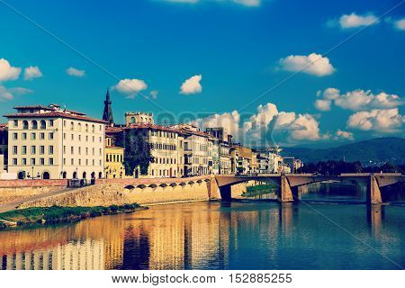 Ponte alle Grazie bridge in Florence, Italy with blue sky, clouds and reflection in the river Arno. Travel outdoor sightseeing background.