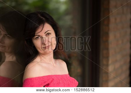 middle aged woman in red dress in front of the window