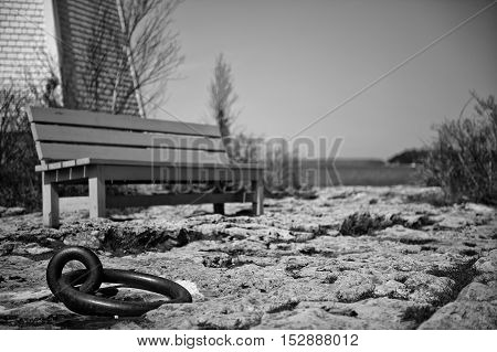 close up of an iron cast mooring with bench in background in big tub coastline of bruce peninsula national park. ontario canada