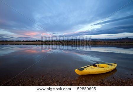 A single yellow kayak sits on the shore of a lake as the clouds start to turn pink at sunrise