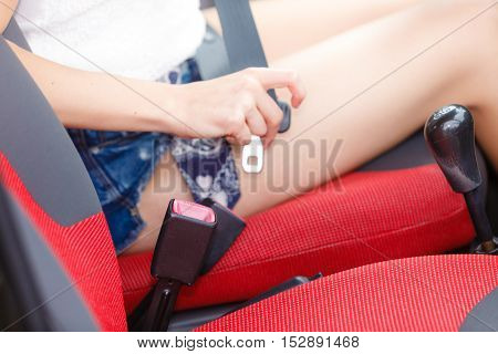 Transportation vehicle and safety concept. Young woman fastening seat belt in car