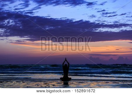 Silhouette young woman practicing lotus yoga on the beach at sunset
