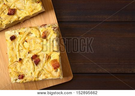 Traditional German Zwiebelkuchen savory onion cake pieces made of onion bacon and cream sauce on yeast dough photographed overhead on dark wood with natural light (Selective Focus Focus on the top of the cake pieces)