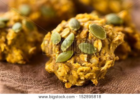 Pumpkin and oatmeal drop cookies with pumpkin seeds on top photographed with natural light (Selective Focus Focus in the middle of the cookie)