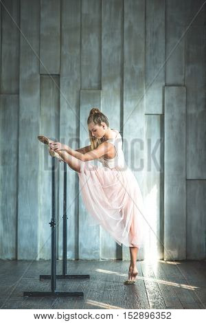 Working on her form. Pretty young graceful ballet dancer warms up in ballet class during stretching, posing at ballet barre