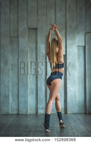Rhythm is life. Rear view of dancing lady in black clothes posing during training in studio