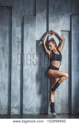 Dancing is a celebration of life. Young beautiful woman in black T-shirt and shorts dancing in studio with gray wall on background
