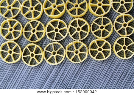 Wagon wheel pasta on a grey background with copy space selective focus.