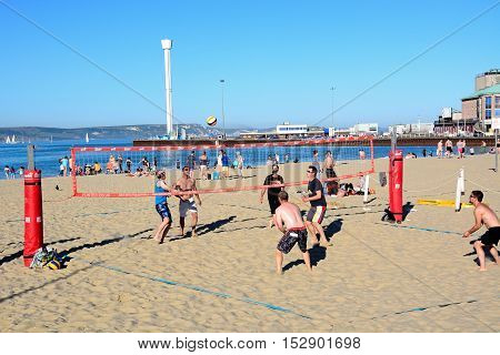 WEYMOUTH, UNITED KINGDOM - JULY 18, 2016 - Holidaymakers playing volleyball on the beach with the Pavilion and Jurassic Skyline tower to the rear Weymouth Dorset England UK Western Europe, July 18, 2016.
