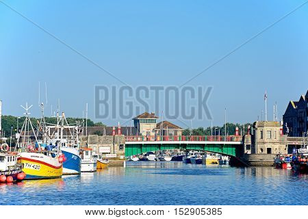 WEYMOUTH, UNITED KINGDOM - JULY 19, 2016 - View of the twin leaf bascule bridge and fishing trawlers in the harbour Weymouth Dorset England UK Western Europe, July 19, 2016.