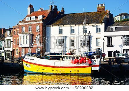 WEYMOUTH, UNITED KINGDOM - JULY 19, 2016 - Fishing trawler moored in the harbour with quayside buildings to the rear Weymouth Dorset England UK Western Europe, July 19, 2016.