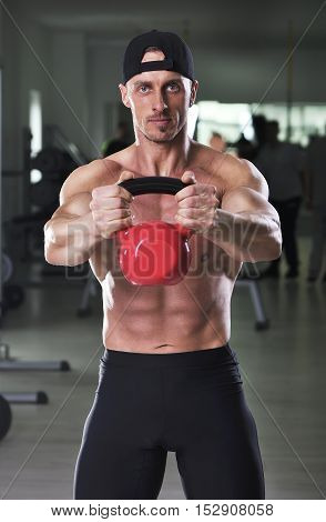 Handsome Powerful Athletic Man Doing Shoulder Exercise With Kettle Bell. Strong Bodybuilder With  Pe