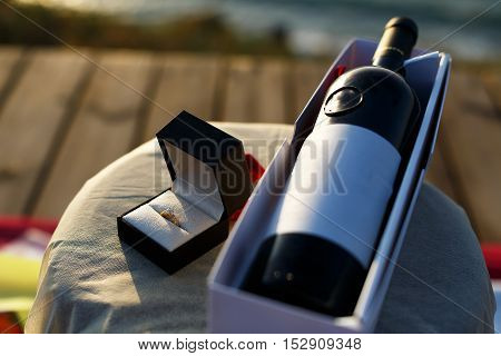 Marriage proposal setup with a ring in a wine glass with a rose and a bottle of wine