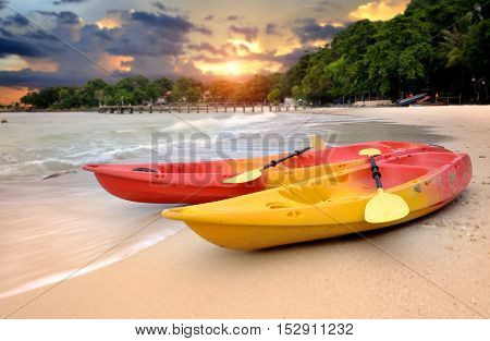 Two kayaks on the beach of the island in warm tone outdoor morning sunrise low lighting.