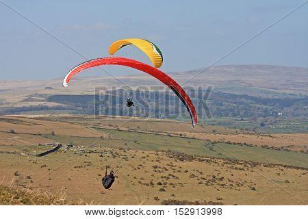 Paragliders flying above Dartmoor in Devon, England