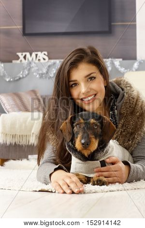 Happy young woman lying on floor with dachshund, smiling, looking at camera.