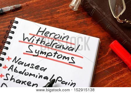 Heroin withdrawal written on a note. Drugs addiction concept.