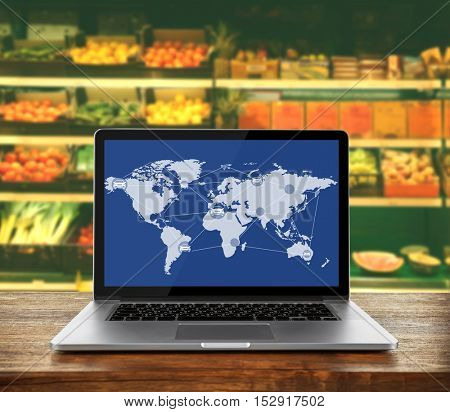 Laptop on wooden table against supermarket interior background. Worldwide transport logistic network on screen. Wholesale and retail concept.