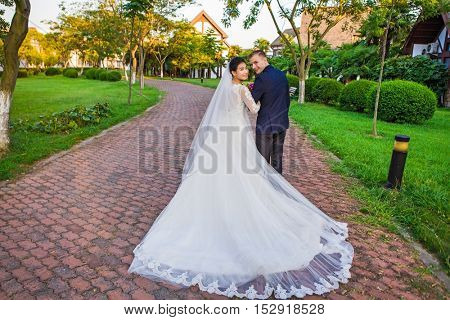 Side view of smiling wedding couple holding bouquet on path