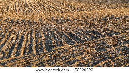 furrows on the surface of ploughed field making interesting shapes useful as background