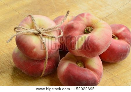 Dough nut peaches also known as Saturn peach with hemp rope on wooden board.