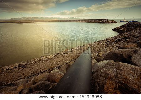 Sewage pipe running into bay of water