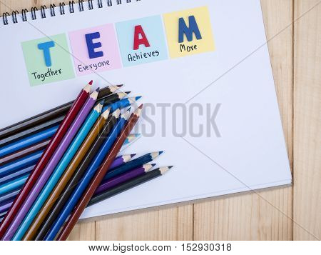 Word spelling TEAM and handwriting together everyone achieve more on notebook with stacl of color pencil (Business Concept)