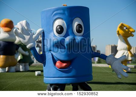 Close up shot of blue mascot character waving at camera