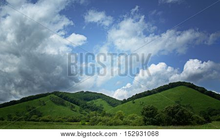 Lush green hiils againsblue sky with wite clouds