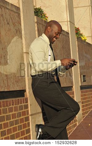 Happy African American business man texting on phone outside office building