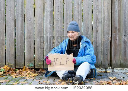 Elderly Homeless Woman Sitting On The Street