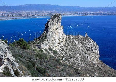 Seascape with a famous rock Sella del Diavolo - the Devil's Saddle the beach il Poetto and the city Cagliari in Sardinia Italy.