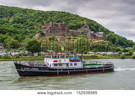 Trechtingshausen Germany - May 23 2016: Tug vessel Josef Langen on the Rhine River near Trechtingshausen in cloudy weather Rhine Valley Rhineland-Palatinate Germany. Reichenstein castle in the background.