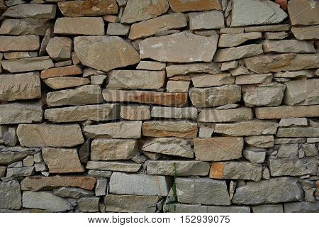A fragment of a wall of sandstone stacked without grout. Texture background