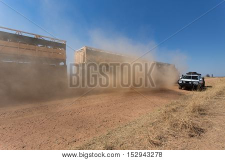 A cattle road train in the outback of Western Australia passes on dusty outback road.