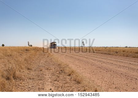A cattle road train in the outback of Western Australia approaches on dusty outback road.