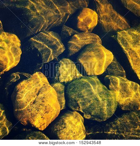 Shallow water with stones in the bottom. Aged photo. Lake Ladoga bottom with pebbles. Ripples on the surface of the stones. Vintage filter photo. Rocks through the water.