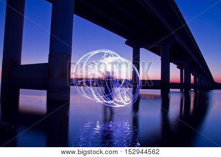 The bridge. A look under the bridge. The bridge over the river. Light orb. The bridge over the river at sunset.
