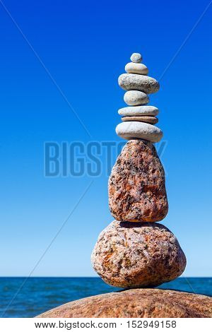 Balance and poise stones against the sea. Rock zen on the background of blue sky