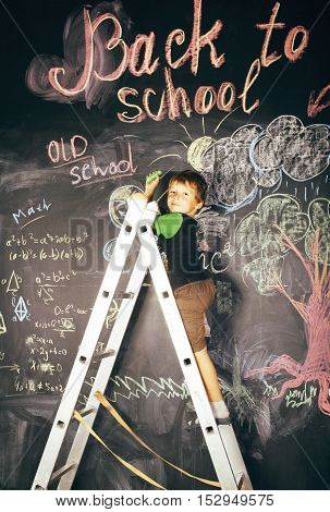 little cute real boy at blackboard in classroom, back to school close up, lifestyle real people concept