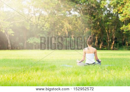 Girl do yoga meditation at the park in the morning with sunlight.