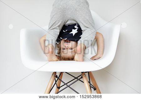 Indoor Portrait Of Beautiful Toddler Dressed In Stylish Pajamas With Stars, Trying To Do Somersault