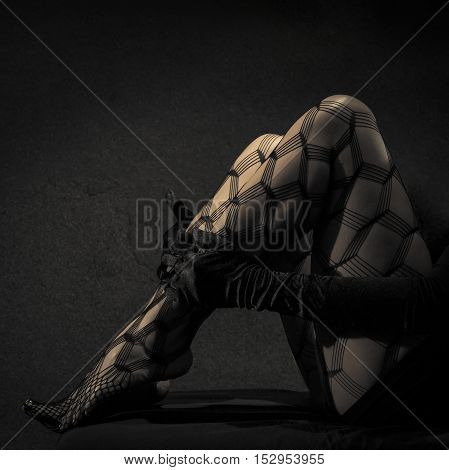 Low key special toned photo of sexy female nude legs in net tights and hands in black leather gloves against dark background